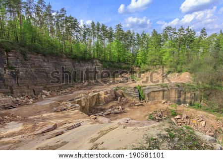 Wide angle view of a quarry with layers of unsurfaced sandstone, and forest and sky in background  - stock photo