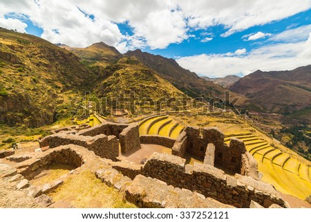 Wide angle view of building and wall ruins with glowing majestic concentric terraces of Pisac, Inca's site in Sacred Valley, major travel destination in Cusco region, Peru. - stock photo