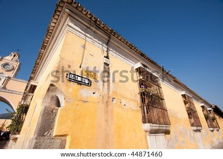 Wide angle view of building corner with the Arco de Santa Catalina in background(left) in Antigua, Guatemala, Central America. - stock photo