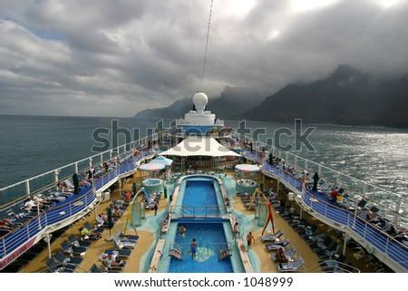 Wide angle view of cruise ship deck sailing along the Na Pali Coast on the island of Kauai in Hawaii. - stock photo