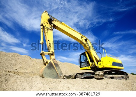 Wide angle view of excavator standing on ground with blue sky and white clouds in background
