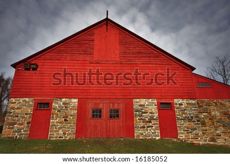 Wide angle view of historic old red wood and stone barn. - stock photo