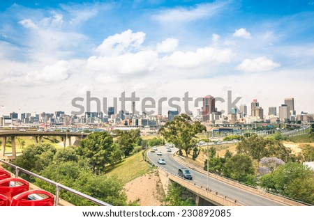 Wide angle view of Johannesburg skyline from the highways during a sightseeing tour around the urban area - Metropolitan buildings of the business district in the capital of South Africa - stock photo