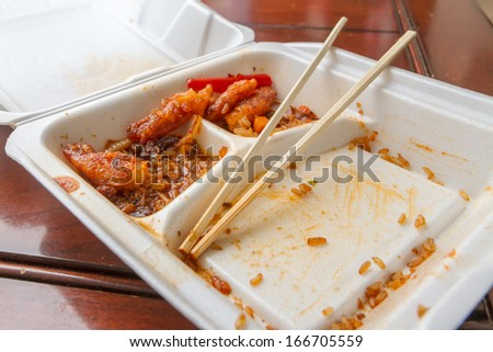 Wide angle view of left over chinese food and chopsticks - stock photo