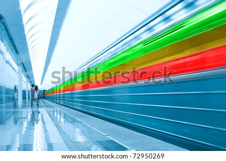 wide angle view of modern metro station with colorful train motion