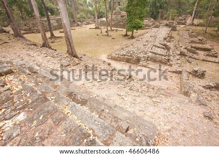 Wide angle view of ruins of residential area surrounded by jungle at the ancient Mayan city of Copan. Honduras, Central America. - stock photo