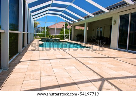wide angle view of screened in pool and lanai in florida with blue sky - stock photo