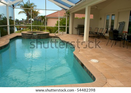 wide angle view of screened in pool and lanai in florida with sitting area - stock photo