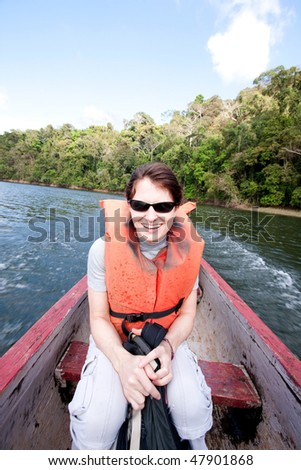 Wide angle view of smiling, young woman in dug out canoe on the Chagres River, Panama, Central America. - stock photo