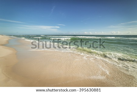 Wide angle view of sparkling waves and surf on a Florida beach on a sunny day - stock photo