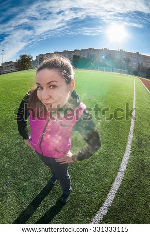 Wide angle view of sporty woman standing on playing field, looking at camera - stock photo