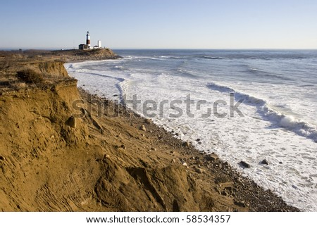 Wide-angle view of the cliffs of Camp Hero to the Montauk Point Lighthouse. The lighthouse overlooks the Atlantic ocean. Long Island, NY - stock photo