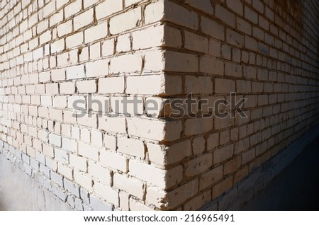 Wide angle view of the corner of a building made of white bricks, shadow and light sides, frame for text, a lot of copyspace