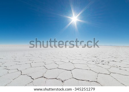 Wide angle view of the world famous Uyuni Salt Flat, among the most important travel destination in the Bolivian Andes. Close up of hexagonal shapes of the salt pans in backlight. - stock photo