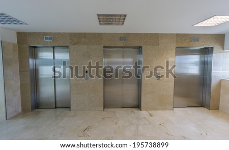 Wide angle view of three modern elevators with closed doors - stock photo