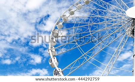 Wide big ferris wheel on blue cloudy wonderful sky - stock photo