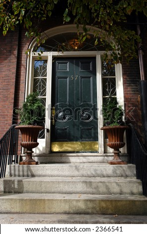 wide black door with brass kick plate, white wood work and terra cotta flower urns - stock photo