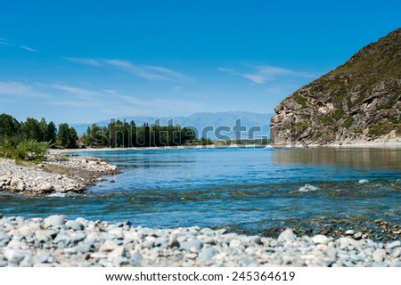 Wide blue river flows in the mountains - stock photo