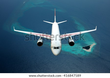 Wide-body passenger jet plane. Aircraft is flying over the deep-blue ocean and Maldives island. - stock photo