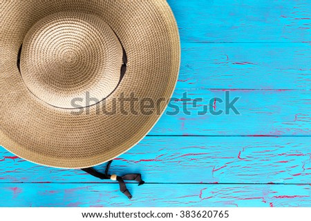 Wide brimmed straw gardening hat on an old weathered colorful blue picnic table with copy space in an overhead view - stock photo