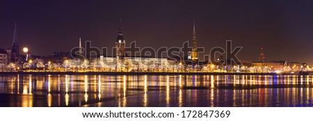 Wide cityscape panorama of Old Riga in night time with rich illumination. - stock photo