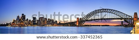 wide colourful panorama of Sydney city CBD landmarks including skyscrapers, Harbour Bridge, houses and harbour at sunset