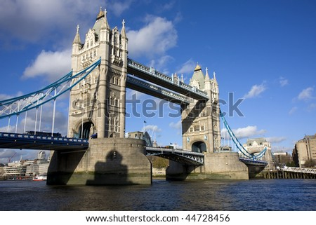 Wide daytime shot of Tower Bridge, London, UK, with a blue sky and white clouds - stock photo