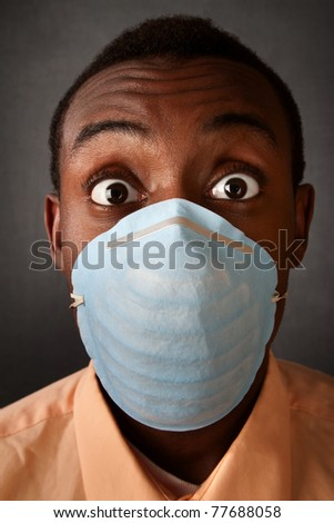 Wide-eyed Black man wearing a surgical mask - stock photo