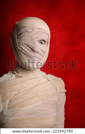 wide-eyed female mummy covered in bandages - stock photo
