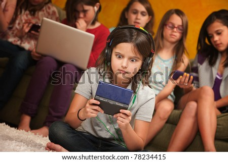 Wide-eyed little girl with headphones and game console with friends - stock photo