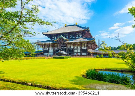 Wide green lawn in front entrance facade on grounds of main Great Buddha Hall, Daibutsuden, on a beautiful, blue sky summer morning at Todai-ji temple in Nara, Japan. Horizontal