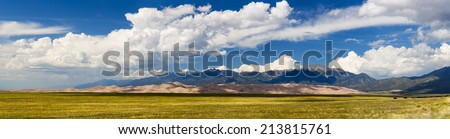 Wide high resolution stitched panorama of the dunes at Great Sand Dunes National Park in Colorado with the mountains behind. Unusual to see clouds over the sand - stock photo