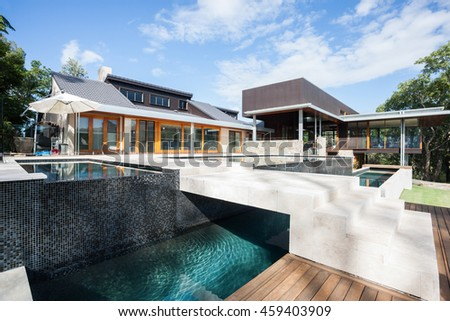 Wide image of a modern mansion or hotel with a river around with a bridge, the sky is blue beside creative building