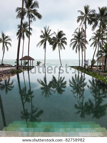 Wide marble steps go down in pool. Smooth water of pool reflects high picturesque palm trees in a beach of Andaman sea - stock photo