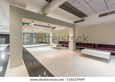 Wide modern corridor with white pillars, white and grey tiles on the floor and purple seats by wall
