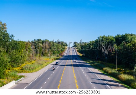 Wide multi-lane road with few cars in wooded area on blue sky. - stock photo