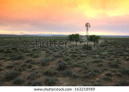 Wide open farm land with a water windmill pump at sunset in the Karoo in South Africa - stock photo