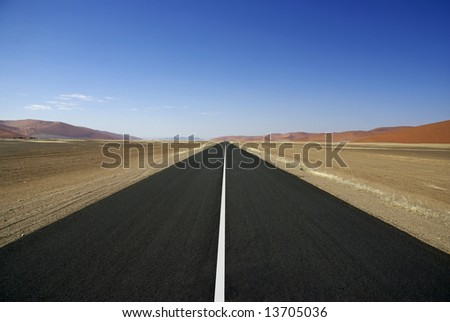 Wide open road in Namibia headed toward the Sossusvlei - stock photo