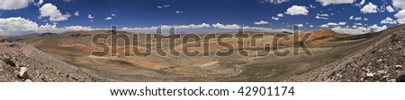 Wide panorama of a rocky desert taken on the northwest region of Argentina. You can see the salt lake far behind the mountains. - stock photo