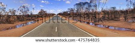 wide panorama of empty remote road across red soil outback laying after bushfire in western australia