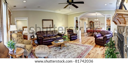 wide panorama of living area and dining area of upscale house - stock photo
