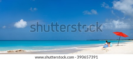 Wide panorama of mother and kids family at tropical beach on summer vacation. A lot of copy space, perfect for banners. - stock photo
