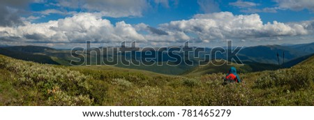 Wide panorama of Mountain Altay with relaxing hiker, Siberia, Russia, Autumn