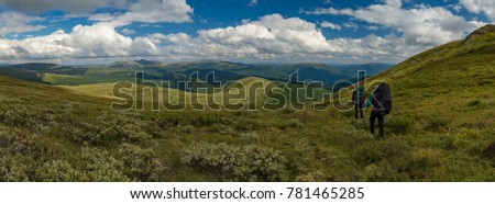 Wide panorama of Mountain Altay with two hikers, Siberia, Russia, Autumn