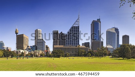 Wide panorama of Sydney city landmark towers and buildings from Royal eye hospital to modern bank offices as seen across green grass of domain park on a bright sunny day.