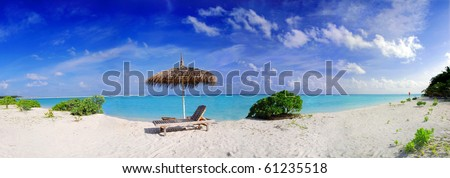 Wide panoramic photo of a beautiful Maldivian beach with parasol and two deck chairs in the front - stock photo