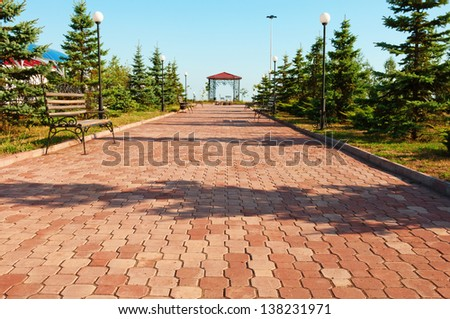 Wide path in nice light  park with benches and summerhouse under clean blue sky - stock photo