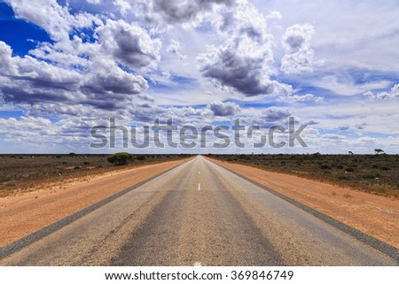 wide perspective view of tarmac road heading towards horizon under sunny summer sky between red soil roadsides with no vehicles around in nullarbor plain of South Australia - stock photo