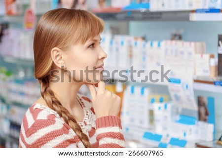 Wide range of beauty products. Young attractive woman looking at the shelves with medications at the pharmacy - stock photo