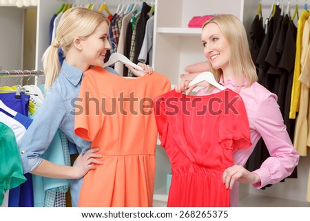 Wide range of fashionable dresses. Nice blond sales consultant and a female shopper trying dresses of different colors and smiling to each other